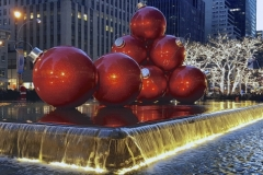 Display of Huge Christmas Ornaments Surrounded By Fountain-Radio City Music Hall In Background